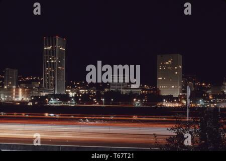 Downtown core area of Portland, after 7pm on November 2 1973, during the state's energy crisis with few commercial and neon lighting displays. This photo looks toward the west with the Willamette river in the foreground. Image courtesy National Archives, United States, 1973. - Stock Photo