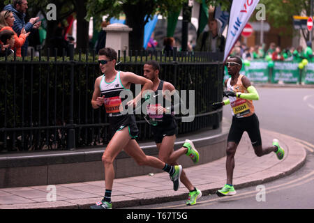 Callum Hawkins (GBR), Yassine Rachik (ITA) and Bashir Abdi (BEL), battling it out around Canary Wharf, during the 2019 London Marathon. They went on to finish 10th, 9th and 7th respectively  in the Men's elite race. - Stock Photo