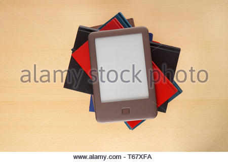 ebook reader on pile of books - Stock Photo