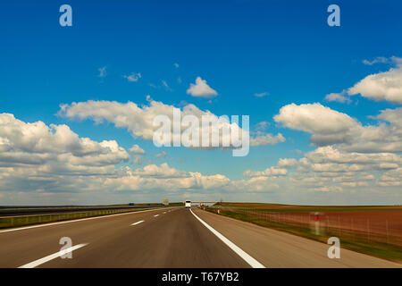 Abstract speed motion on highway background image through countryside with beautiful clouds - Stock Photo