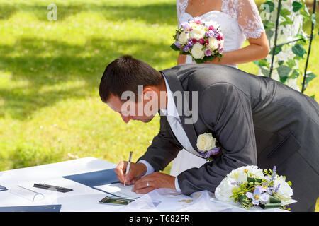 groom signing certificate in park - Stock Photo