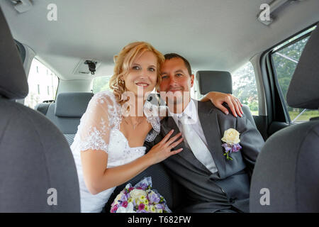 beautiful young wedding couple in car
