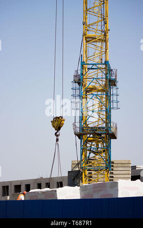 the worker and the crane operator unload the car with reinforced concrete walls for the future high-rise building. reportage shooting. - Stock Photo