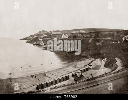 Late 19th Century view of bathing huts on a beach at Howth, a fishing village and outer suburb of Dublin, Ireland. Originally just a small fishing village, Howth with its surrounding once-rural district is now a busy suburb of Dublin, with a mix of suburban residential development, wild hillside and heathland, golf courses, cliff and coastal paths, a small quarry and a busy commercial fishing port. - Stock Photo