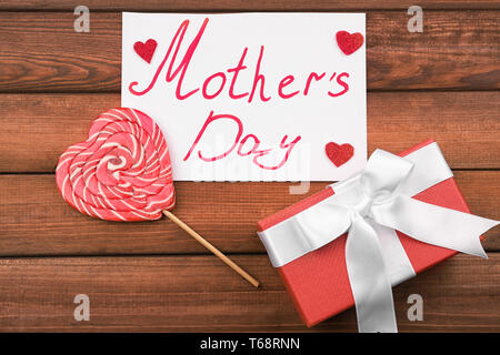 Gift box with greeting card for Mother's Day on wooden background - Stock Photo
