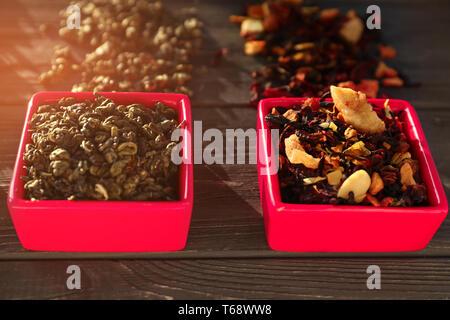 Bowls with different types of dry tea leaves on wooden background - Stock Photo
