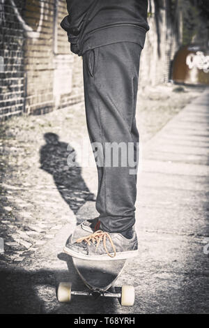 vintage shoot of a teenager standing on a long board - Stock Photo