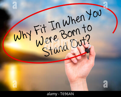 Man Hand writing Why Fit In When You Were Born to Stand Out? with black marker on visual screen. - Stock Photo