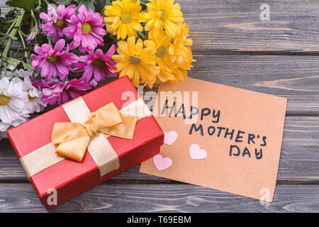 Gift box with flowers and greeting card for Mother's Day on wooden background - Stock Photo