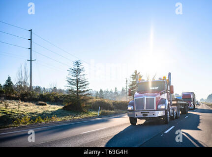 Red big rig industrial grade freight transportation semi truck transporting commercial cargo on flat bed semi trailer running in front of semi trucks  - Stock Photo