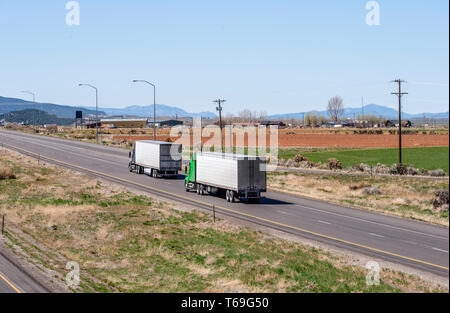 Two big rig industrial grade American freight transportation semi trucks transporting perishable commercial cargo at reefer semi trailers running on t - Stock Photo