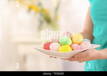 Young woman with plate full of colorful Easter eggs, closeup - Stock Photo