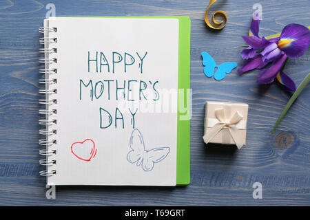 Notebook with written text HAPPY MOTHER'S DAY, gift and flower on wooden table - Stock Photo