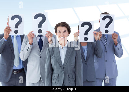 Composite image of business colleagues hiding their face with question mark sign - Stock Photo