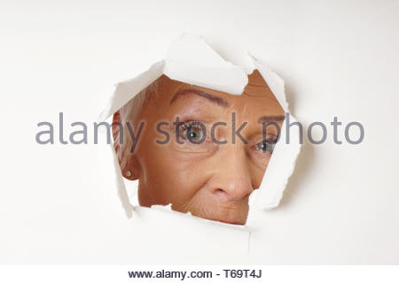 watchful older woman looking through hole - Stock Photo