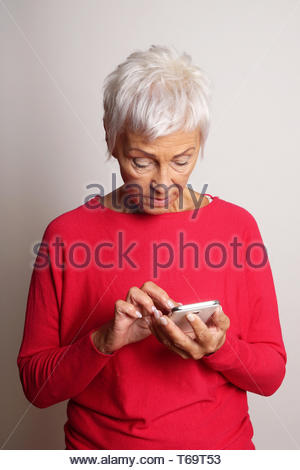 confused senior woman using smartphone - Stock Photo
