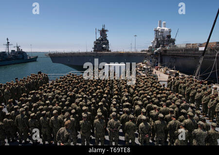 SAN DIEGO (April 26, 2019) The crew of the amphibious assault ship USS Bonhomme Richard (LHD 6), observes as Rear Adm. Cedric Pringle, Commander, Expeditionary Strike Group (ESG) 3, awards Religious Programs Specialist Seaman David Miller, from Salem, N.H., assigned to Bonhomme Richard, with the Navy and Marine Corps Commendation Medal during an awards ceremony on the roof of the ship's barge. Miller was awarded for his efforts in apprehending a woman threatening a church congregation on April 20, 2019. Bonhomme Richard is in its homeport of San Diego. (U.S. Navy photo by Mass Communication Sp - Stock Photo
