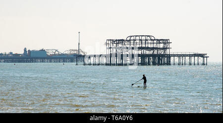 Brighton UK 30th April 2019 - A paddle boarder enjoys the warm sunny weather off Hove beach near the West Pier this morning with it forecast to reach into the high teens in some parts of the South East today. Credit: Simon Dack/Alamy Live News - Stock Photo