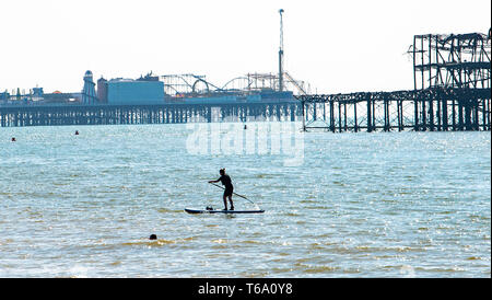 Brighton UK 30th April 2019 - A paddle boarder and swimmer enjoy the warm sunny weather off Hove beach near the West Pier this morning with it forecast to reach into the high teens in some parts of the South East today. Credit: Simon Dack/Alamy Live News - Stock Photo