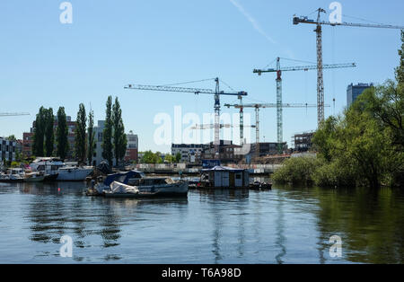 Berlin, Germany. 30th Apr, 2019. Panoramic view over Lake Rummelsburg to new buildings and construction cranes on the peninsula Stralau at the bay of Rummelsburg. The development plan for the Rummelsburger Bucht with the tourist attraction 'Coral World' has been approved. In addition, office space, privately financed apartments and 110 rent-linked apartments are planned. Credit: Jens Kalaene/dpa-Zentralbild/ZB/dpa/Alamy Live News - Stock Photo
