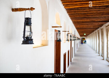 Landscape photo of a series of kerosene lamp in one of the open-air corridor forming a one point perspective in the Qasr Al-Hosn Fort in Abu Dhabi, Un - Stock Photo