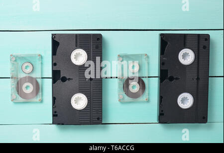 Video cassettes and audio cassettes on a turquoise wooden table. Retro video and audio technology. Top view. - Stock Photo