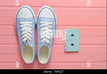 Audio cassette and sneakers shoes on a pink pastel background. Old-fashioned technologies. Top view. Flat lay. - Stock Photo