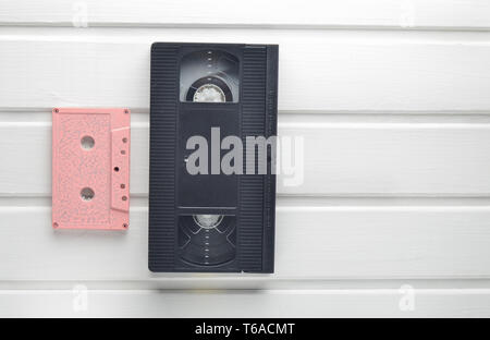 Video cassette and audio cassette on a white wooden table. Retro video and audio technology. Top view. - Stock Photo