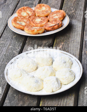 Traditionally, Russian raw and fried pancakes with cottage cheese. Cheesecakes on a wooden rustic table. The cooking process. - Stock Photo