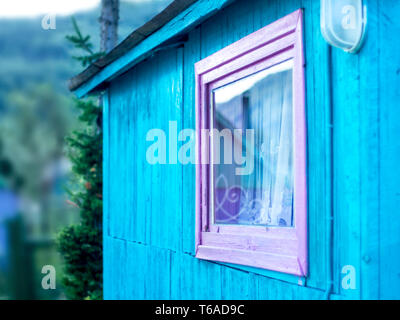 Minimalist Design Concept: Vivid Purple Window Frame, a Light on Blue Wall of Wooden Planks. Mountain Reflection in Glass, White Curtain. Roof Eaves - Stock Photo