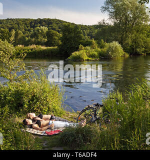 two young women relaxing at river Ruhr in Bochum, Germany, North Rhine-Westphalia, Ruhr Area, Bochum - Stock Photo