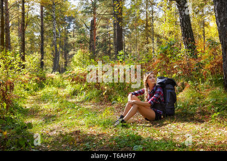 Young blonde tourist  woman with a backpack sitting on the sidelines of the forest path - Stock Photo
