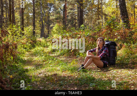 Young blonde tourist  girl with a backpack sitting on the sidelines of the forest path - Stock Photo