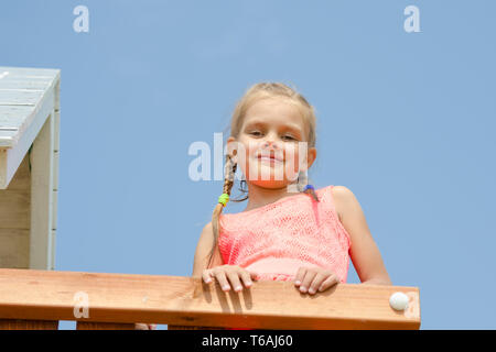 Happy girl climbed on the playground and looked down smiling - Stock Photo