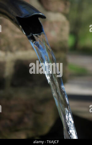 Close up of running water from a metal tap - Stock Photo