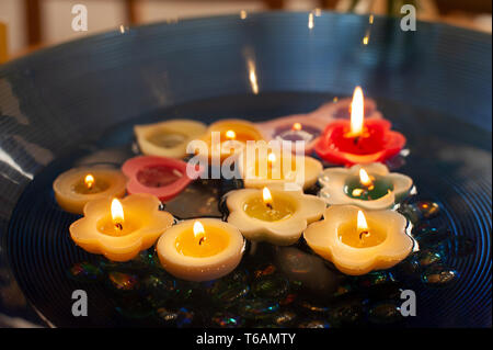 Floating small candles floating in large water bowl, a clm and reflective mood to remember lost and dying friends and family receiving medical care - Stock Photo