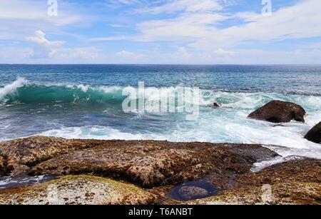 Beautiful splashing turquoise ocean waves at the white beaches on the paradise island Seychelles - Stock Photo