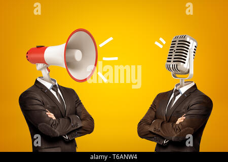 Waist-deep view of two businessmen standing in half-turn, arms folded, with megaphone and microphone instead of heads. - Stock Photo