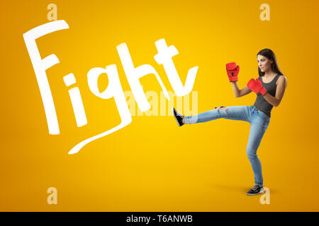 Side view of young pretty girl in jeans, sleeveless top and red boxing gloves with leg lifted for a kick on yellow background with Fight title. - Stock Photo