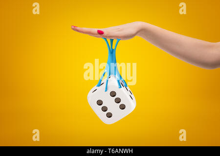3d rendering of casino dice stuck with sticky slime to female hand on yellow background - Stock Photo