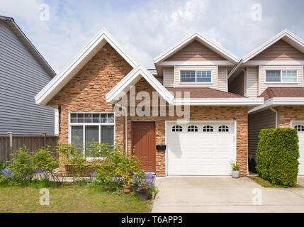Half of residential duplex building with concrete driveway - Stock Photo