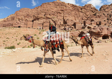 A Bedouin man riding his camel in the ancient city of Petra, Jordan. - Stock Photo
