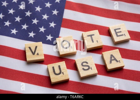 Maski, India 26, April 2019 : Vote USA wooden block letters on US flag - Stock Photo