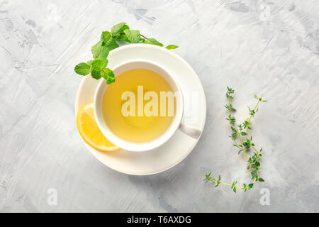 A cup of green tea with lemon, shot from above with mint, thyme, and copy space - Stock Photo