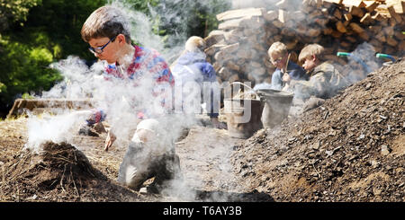 boys with smoking charcoal pile, Ennepetal, Ruhr Area, North Rhine-Westphalia, Germany - Stock Photo