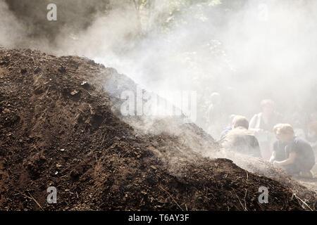 smoking charcoal pile, Ennepetal, Ruhr Area, North Rhine-Westphalia, Germany - Stock Photo