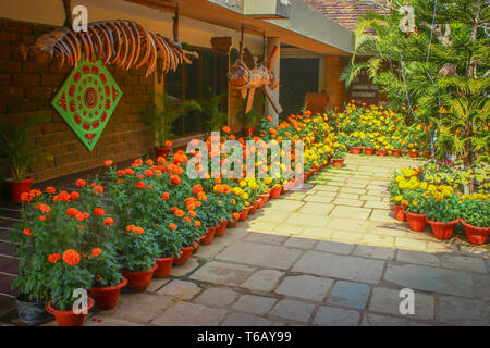 The entrance to a hotel motel surrounded by beautiful flowers kept in vases in Mumbai, India - Stock Photo