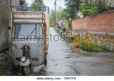 Srinagar, Jammu and Kashmir, India: Dated- March 20, 2019- A three wheeler autorickshaw parked on the side of a wet road on a rainy day in Kashmir - Stock Photo
