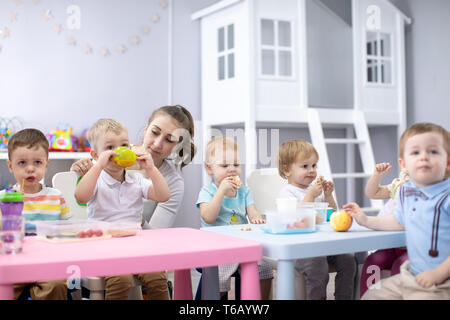 Group of kids having lunch in nursery or daycare centre - Stock Photo