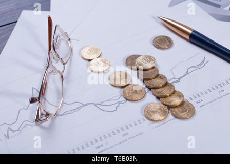 Lying on financial charts glasses, pen and scattered coins - Stock Photo